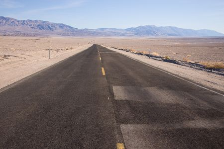 Death Valley  is the lowest, driest and hottest valley in the United States.  This highway leads through the desert landscape. photo