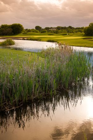 A view of the water and marsh near a golf course.  The dramatic sky and reflections give a peaceful feeling.