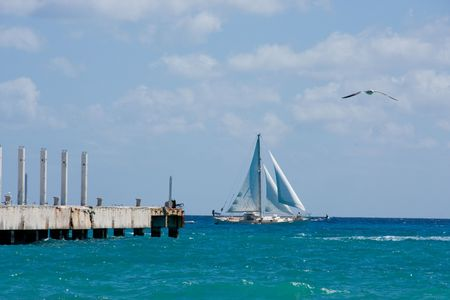 carmen: A sailboat sailing by just beyond the pier in Playa Del Carmen, Mexico.