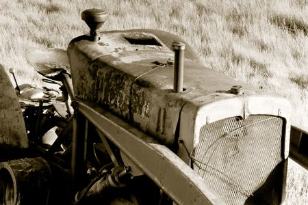 An old tractor rusting away on the prairie landscape.  Sepia tone applied to photo.