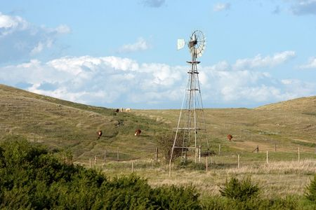 A windmill and cows grazing on the rolling hills of the Canadian Prairies. Stock Photo - 5200954