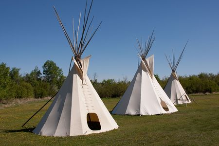 tipi: A small group of teepees in a meadow surrounded by forest. Teepees were traditional housing for Native Americans in Great Plains and other Western states. Stock Photo