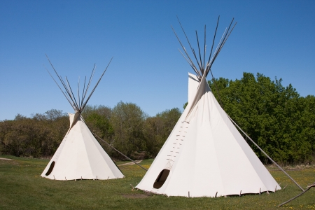 cree: A small group of teepees in a meadow surrounded by forest. Teepees were traditional housing for Native Americans in Great Plains and other Western states. Stock Photo