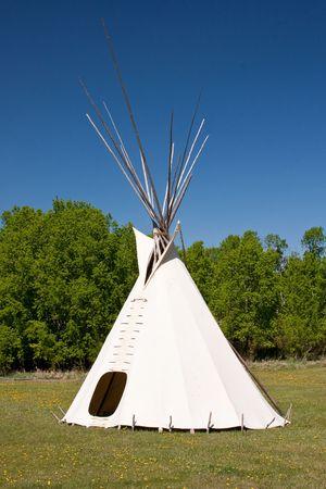 Niewielka grupa teepees na łące, w otoczeniu lasu. Teepees były tradycyjnymi mieszkań dla Indian w Great Plains i innych państw zachodnich.