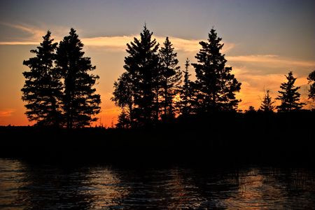 Sunset glow beyond a northern Canadian lake at twilight with the silhouette of trees in the foreground.  Stock Photo - 6282876