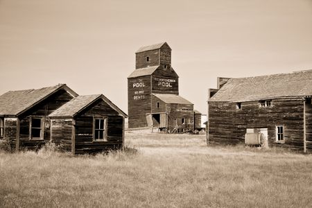 Prairie ghost town where a grain elevator and a couple of buildings still stand.  photo
