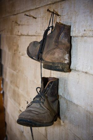 are working: Pair of old boots hanging on the wall Stock Photo