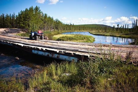 evergreen forest: Bridge crossing on a Northern Canadian river in the thick evergreen forest. Stock Photo