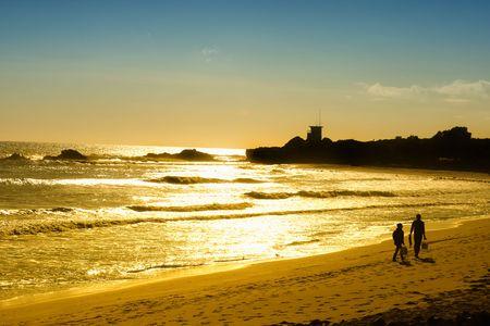 Zachód słońca na Pacyfiku, podczas gdy kilka walk on the Malibu beach w Kalifornii