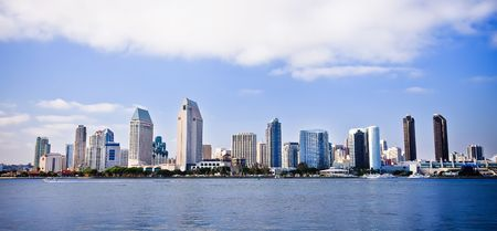 San Diego city skyline at sunset, showing the buildings of downtown rising above harbor viewed from Coronado Island.