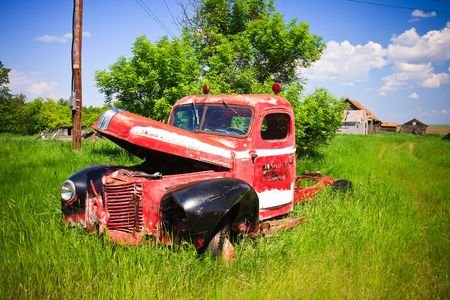 abandoned car: Old rusty red farm truck fading in time.