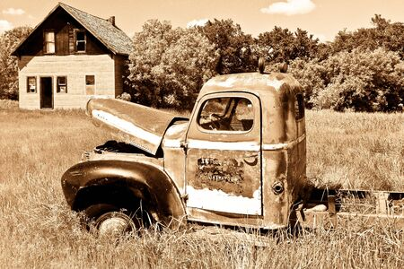 Old rusty red farm truck fading in time.