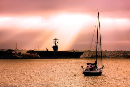 Sun shining through the cloud on the Ronald Reagan Aircraft Carrier in the bay of San Diego, California. photo