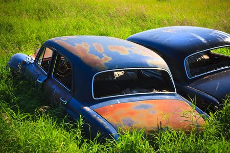 Old abandoned car rusting in the tall green grass Banque d'images
