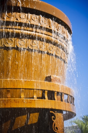 Large golden bucket with water overflowing out of it. Stok Fotoğraf