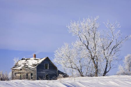 Old abandoned farm house in a frosty winter wonderland photo