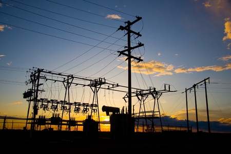 electric power station: Power poles and transmission lines at sunset.