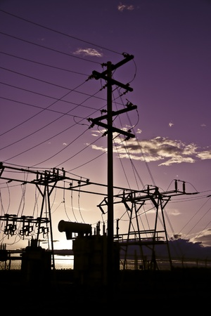 Power poles and transmission lines at sunset.