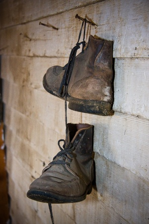 dirty feet: Pair of old boots hanging on the wall Stock Photo