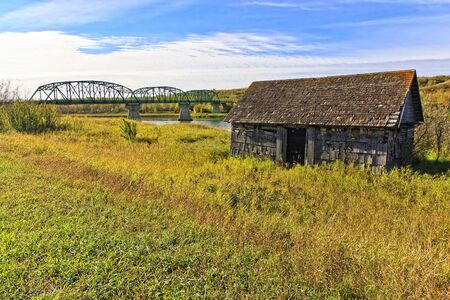 Rustic old abandoned house near the banks of the river near a green bridge. Stock Photo - 9454239