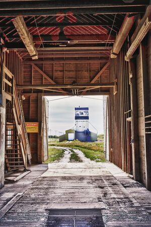 View through one old grain elevator looking at another one down the road. photo