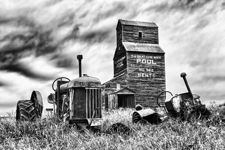 Old abandoned tractor near a grain elevator in the ghost town of Bents in central Saskatchewan, Canada Banco de Imagens