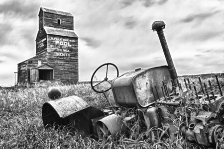 farm structures: Old abandoned tractor near a grain elevator in the ghost town of Bents in central Saskatchewan, Canada Stock Photo