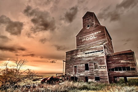 Old abandoned tractor near a grain elevator in the ghost town of Bents in central Saskatchewan, Canada Archivio Fotografico