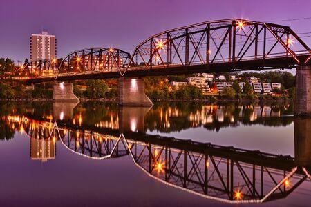 The Victoria Bridge in Saskatoon reflecting in the calm waters of the Saskatchewan River.
