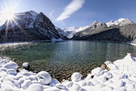 冬のレイクルイーズ、アルバータ州、カナダのロッキー山脈の上輝く太陽 写真素材