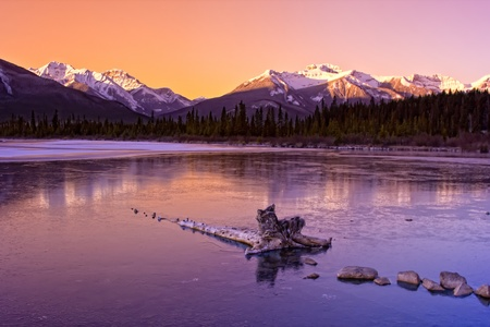 Sunrise over the frozen waters of the Vermillion Lakes with Rocky Mountains in the distance near Banff, Alberta, Canada.