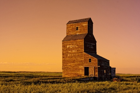 Abandoned grain elevator in the ghost town of Bents on the Canadian prairies during a golden sunset photo