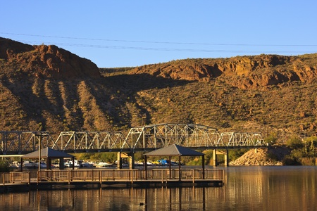 Dock and white steel bridge cross a calm river in the desert. Stock Photo - 12553369