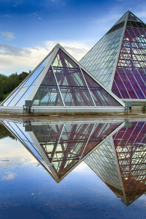Glass pyramids used as a botanical gardens.  The still water makes for a great mirror. Stock Photo - 19739450