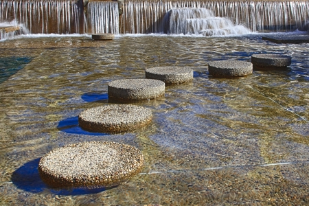 Round stepping stones in front of a waterfall photo