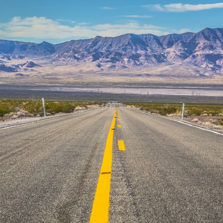 nevada: Long desert highway to the mountains under the hot sun