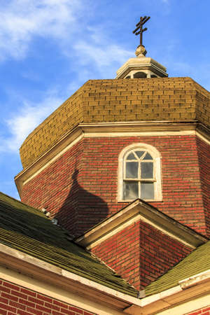 An old red brick church in summer