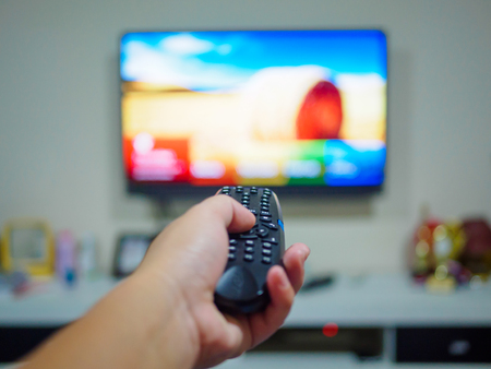 Close up Hand holding TV remote control with a television in the background. Stock Photo