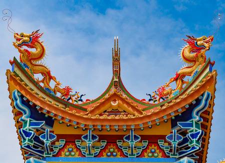 Golden Dragon sculpture on the roof with beautiful color and blue sky background