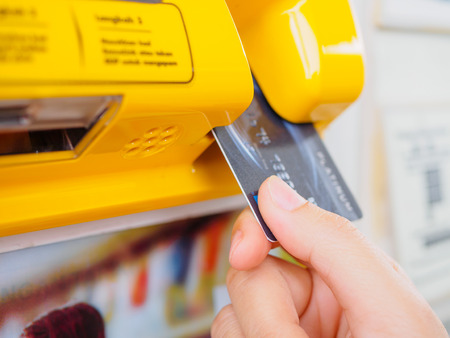 Hand is holding the credit card and insert to the machine Stock Photo