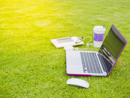 Laptop, notebook, smart phone and stack of old tattered book on the green grass Stockfoto