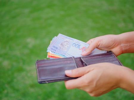 緑の芝生のフィールドに財布からお金マレーシア リンギを取り出し女性手