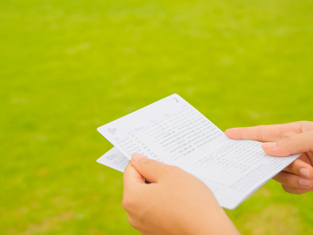 Manos sosteniendo la libreta de la cuenta de ahorro, banco del libro en el fondo de la hierba verde Foto de archivo - 75688920
