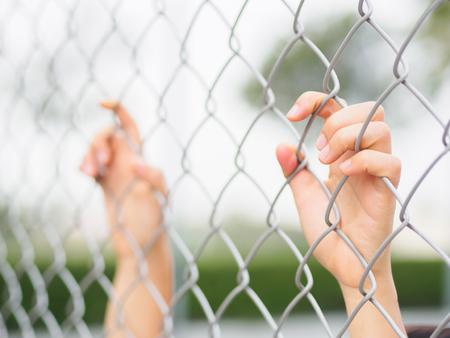 女性の手が屋外の景色の日光の間にフェンスを保持しています。終身刑の刑務所の手
