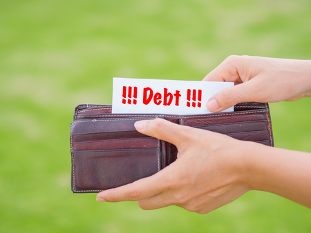 trouble free: Women Hands taking out debt paper from wallet on the green grass field Stock Photo