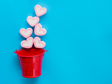 Marshmallow in a red bucket on Valentines Day love concept on blue sky background Stock Photo