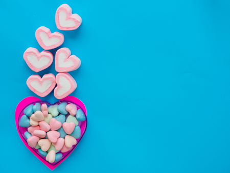 Marshmallow in a heart frame on Valentines Day love concept on blue sky background
