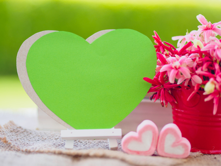 Poster mock up template with flower bouquet, marshmallow in the shape of heart and books over green background Stock Photo