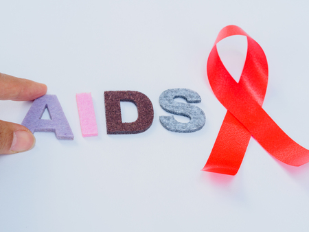 World AIDS day concept. red ribbon with hand holding AIDS text
