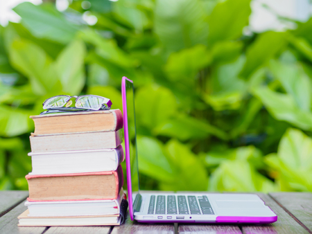 Stack of books with laptop on wood table outdoor Stock Photo